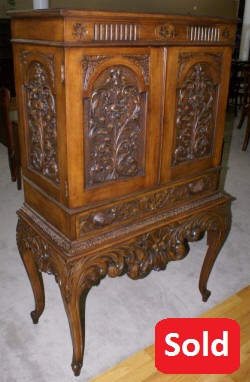 Heavily carved antique walnut blind door crystal cabinet