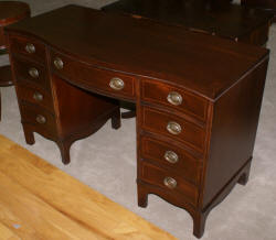 Mahogany pencil inlaid serpentine front antique desk